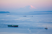 Three tugboats pull barges across the Strait of Juan de Fuca at sunset, with Mount Rainier in the background, as seen from Fort Ebey State Park, Whidbey Island, Washington.