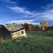 A rickety old farmhouse in a field in MIneesota.