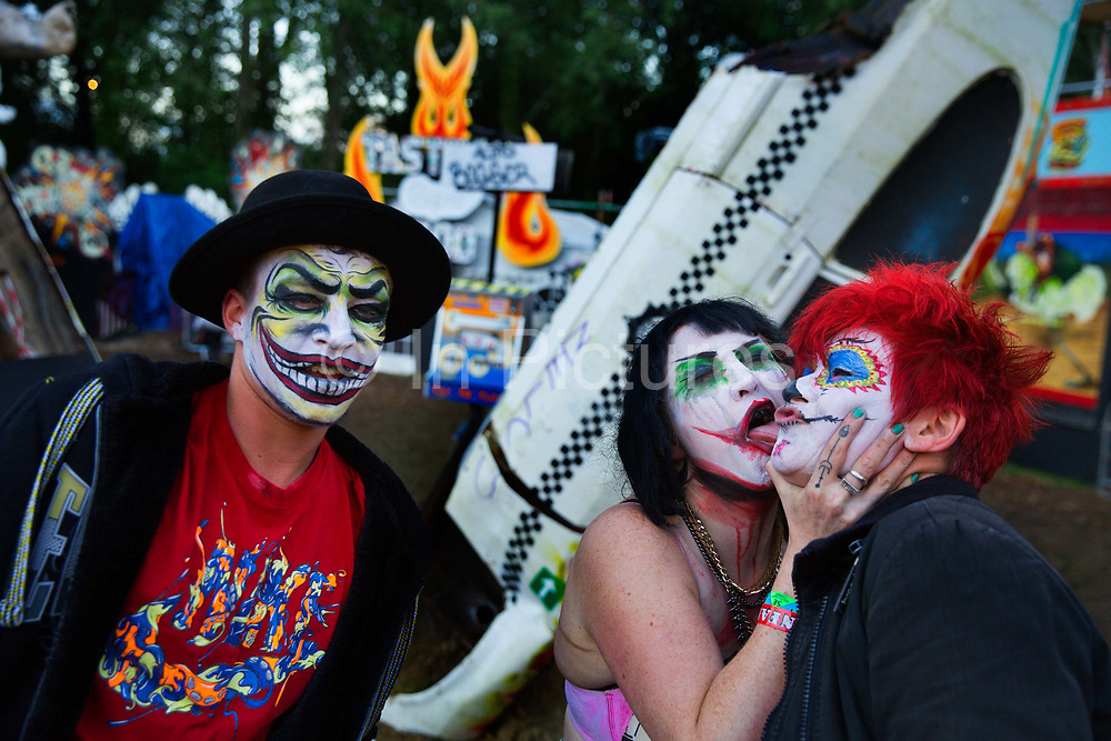 Fun in the Unfairground with kissing clowns, Glastonbury Festival 2016. Glastonbury Festival is the largest greenfield festival in the world, and is now attended by around 175,000 people. Its a five-day music festival that takes place near Pilton, Somerset, United Kingdom. In addition to contemporary music, the festival hosts dance, comedy, theatre, circus, cabaret, and other arts. Held at Worthy Farm in Pilton, leading pop and rock artists have headlined, alongside thousands of others appearing on smaller stages and performance areas.