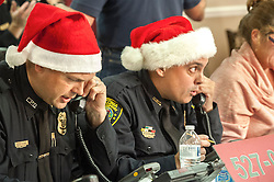 Laconia Police Chief Chris Adams and Lt. Al Lessard take phone bids during the evening session of the annual Children's Christmas Auction on Friday, December 7, 2012.  (Alan MacRae/for the Laconia Daily Sun)