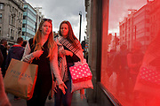 Tinted red from the Top Shop window display, two young women shoppers carry their purchases in Oxford Street, central London. The two modern-looking girls are in their element with shopping bags at the elbows and the red glow from the light shining on their young faces. The woman in front has a long arm with fingers echoing the tassels on her girlfriend's scarf.