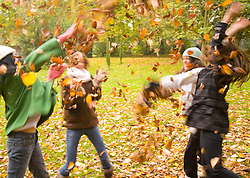 Young girls playing with leaves in the park