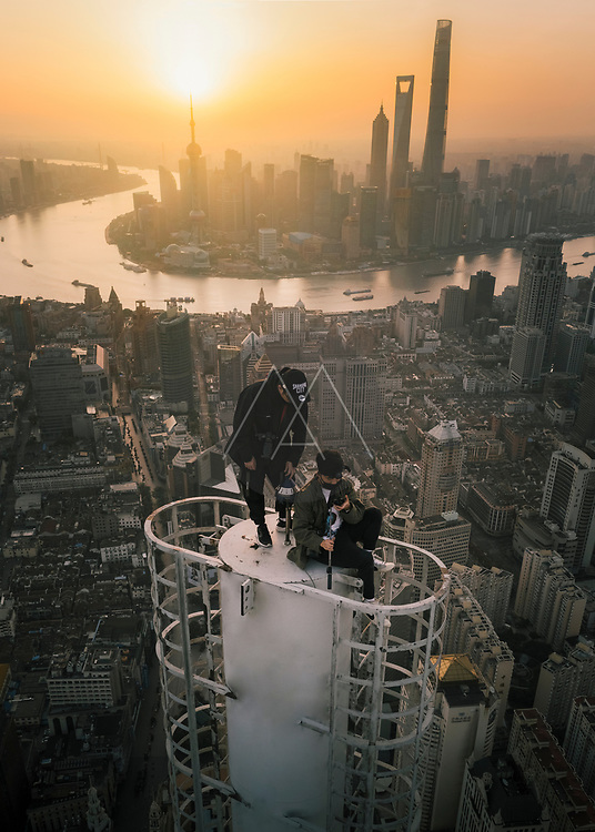 Shanghai, China - 27 April 2019: Aerial view of two young guys standing on the top of a skyscraper with Shanghai with city skyline in background at sunset, Shanghai, China.