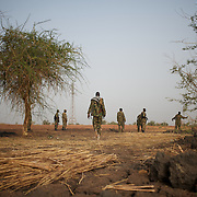 April 24, 2012 - Panakuach, South Sudan: A group of SPLA soldiers walk by in the last defensive line outside the village of Panakuach, 70 kilometers north of Bentiu...South Sudan and their northern neighbors, Sudan, have in the past two weeks been involved in heavily clashes over border disputes. Bentiu and neighboring villages have been under constant bombardment by the troops os Karthoum , who established their positions around 10 kilometers into South Sudan's territory. The international community is concerned about the possibility of a full on war between the two countries. (Paulo Nunes dos Santos/Polaris)