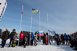 Raising of the flags at the Baikal Mile Ice Speed Festival opening ceremonies where participants on the big stage were introduced to the crowd one at a time. Maksimiha, Siberia, Russia. Saturday, February 29, 2020. Photography ©2020 Michael Lichter.