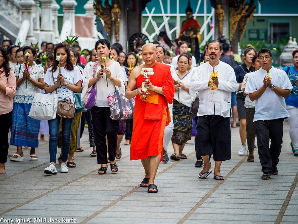 29 MAY 2018 - BANGKOK, THAILAND: A Buddhist monk leads a procession around the prayer hall during Vesak observances at Wat Hua Lamphong in Bangkok. Vesak is the Buddha's birthday, and one of the most important holy days in the Theravada Buddhist religion. Many Thais visit their local temples for Vesak and rededicate themselves to the Dharma, listen to talks about Buddhism and make merit by bringing flowers to the temple.       PHOTO BY JACK KURTZ