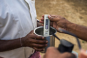 Rajeshwar Thouti, the field executive for Modern Architects for Rural India (MARI), tests the well water from a villager's home in Gorikathapalli, a remote village in Warangal, Telangana, India, on 22nd March 2015. Safe Water Network works with local communities that live beyond the water pipeline to establish sustainable and reliable water treatment stations within their villages to provide potable and safe water to the communities at a nominal cost. Photo by Suzanne Lee/Panos Pictures for Safe Water Network