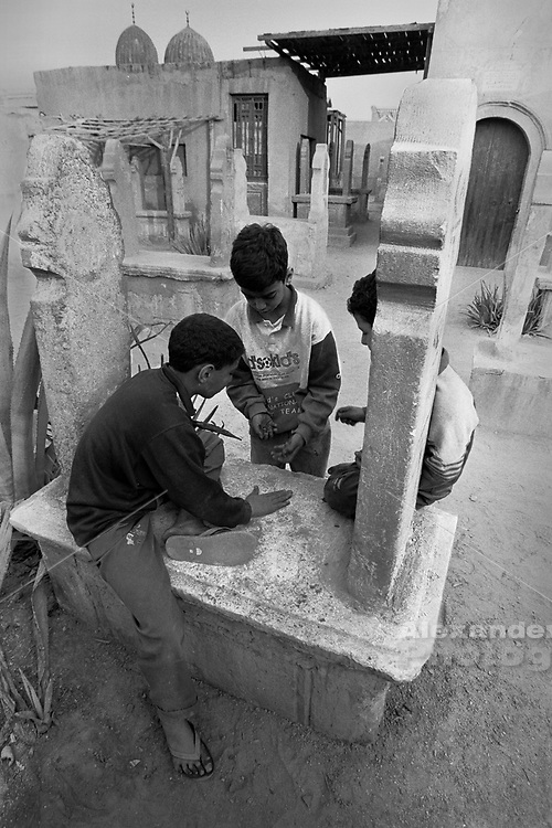 Cairo, Egypt, The City of the Dead, 2000 - Boys play marbles on top of a grave.