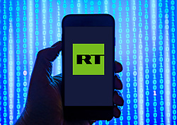 Person holding smart phone with  RT news service  logo displayed on the screen. EDITORIAL USE ONLY