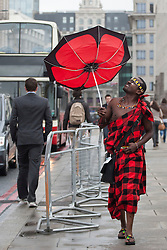 © licensed to London News Pictures. London, UK 01/01/2000. Lloyd Benson walking with an umbrella under the rain after handing out tea gift packages from Kenya to London commuters to celebrate Queen?s Diamond Jubilee this morning on London Bridge. Photo credit: Tolga Akmen/LNP