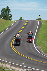 Lichter Sturgis 2015 crew Melissa Shoemaker riding her Street Glide and Garrett Stanley riding Shannon Kerr on his Harley-Davidson Classic in the hills during the 75th Annual Sturgis Black Hills Motorcycle Rally.  SD, USA.  August 8, 2015.  Photography ©2015 Michael Lichter.