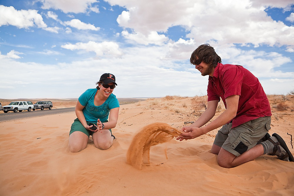 Katy Barnhart and Leif Anderson, students on a geology field trip with the University of Colorado, play with sand in Southern Utah.