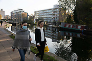 Two women walk along Regents Canal in Hackney during the second coronavirus national lockdownon on 7th of November 2020, East London, United Kingdom. It is the third day of the national lockdown and the lockdown restrictions mean that people are only allowed to meet outside, in pairs and only if keeping social distance. Only if they already live together or have formed a social bubble can they interact freely.