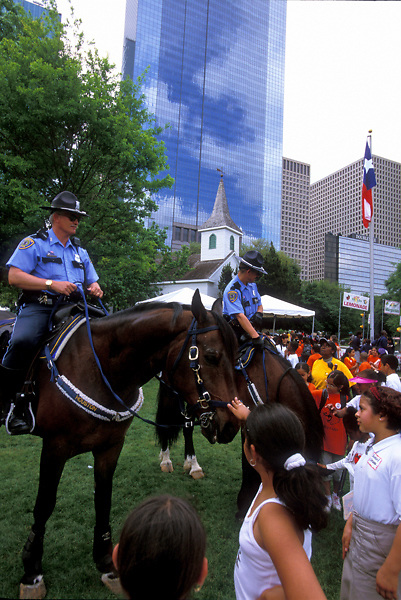 Stock photo of Houston police officers on horseback letting children see and pet their horses in a downtown Houston park