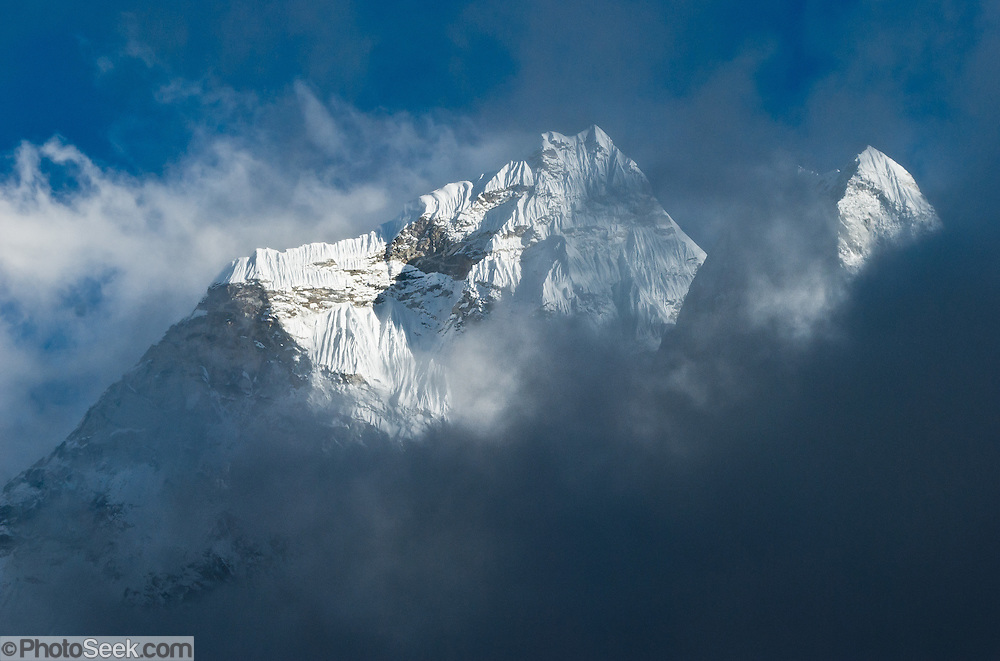 """Sagarmatha National Park: This is the north side of Ama Dablam, a beautiful mountain in the Himalaya range of eastern Nepal, in the Khumbu District. This was photographed between Dingboche and Chhukhung, in the Imja Khola river valley. Ama Dablam was first climbed in 1961. The main peak is 22,349 feet (or 6,812 meters) tall, and the lower western peak is 18,251 feet (or 5,563 meters). Ama Dablam means """"Mother and Pearl Necklace"""" (the pearl being the perennial hanging glacier). Sagarmatha National Park was created in 1976 and honored as a UNESCO World Heritage Site in 1979. Published in """"Light Travel: Photography on the Go"""" book by Tom Dempsey 2009, 2010."""