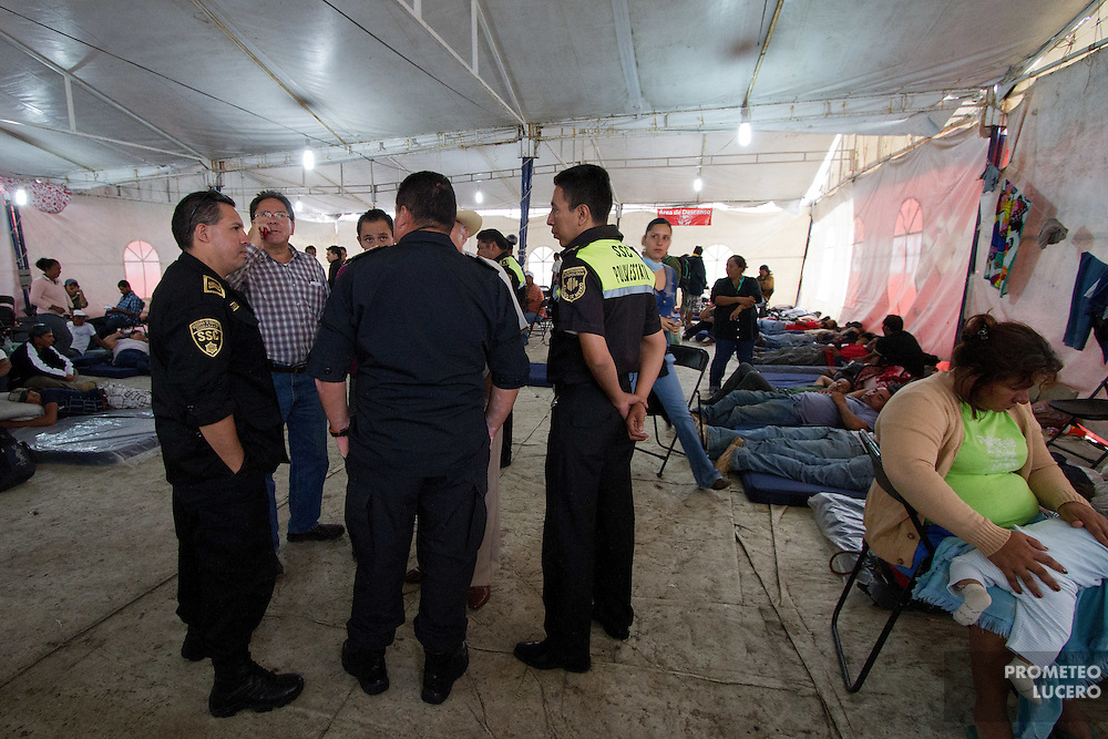 """State police officers and local authorities stand inside the migrants temporary shelter in Tultitlán before asking migrants to leave the place, on on August 3rd, 2012. Tultitlán local authorithies ordered to dismantle the temporary shelter that was placed under a bridge in Tultitlán after shelter  """"San Juan Diego Cuauhtlatoatzin"""" in Lecheria, was closed on July 9th, 2012. (Photo: Prometeo Lucero)"""