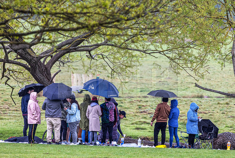 Licensed to London News Pictures. 16/05/2021. London, UK. Picnickers gather with umbrellas and rain coats as they brave the rain in Richmond Park, South West London as miserable May continues with grey skies and yet more rain with temperatures down to 13c. Weather forecasters predict yet more showers for the rest of the weekend and into next week as the bad Spring weather continues. Photo credit: Alex Lentati/LNP