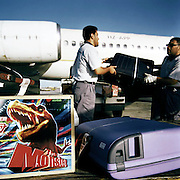 With suitcases and a dinosaur toy box in the foreground, two baggage-handlers manhandle bags onto a Saudi Airlines McDonnell-Douglas MD90-30 (registered as HZ-APP) on the apron at Bahrain airport. In the foreground is a box containing a toy dinosaur called The Monster which is too large to be cabin baggage, instead having to travel in the hold along with cargo and the luggage of other passengers on this flight operated by Saudi and departing from this Gulf state seen here 12 months before the terrorist attacks on America that changed the public's attitude to flying on commercial airliners.