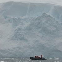 A Zodiac raft carries tourists under a calving glacier face in Neko Harbor, Antarctica.