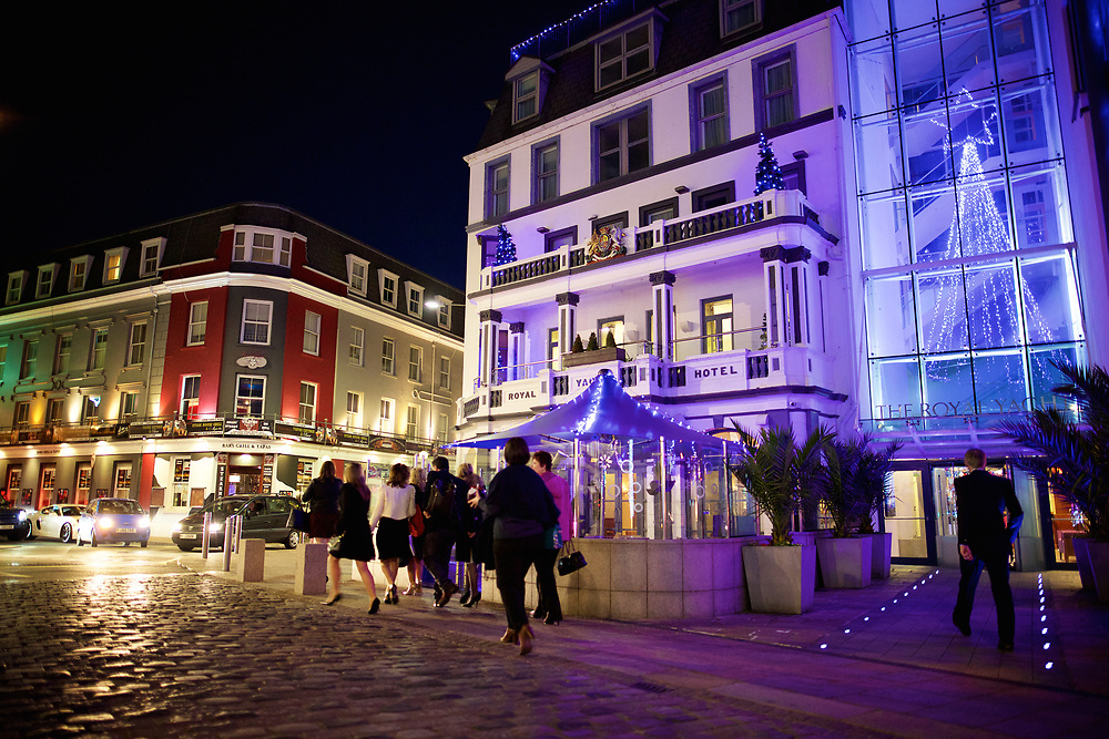 People walking by the Royal Yacht Hotel and Wildfire Bar and restaurant at the Weighbridge Square, St Helier, Jersey at Christmas