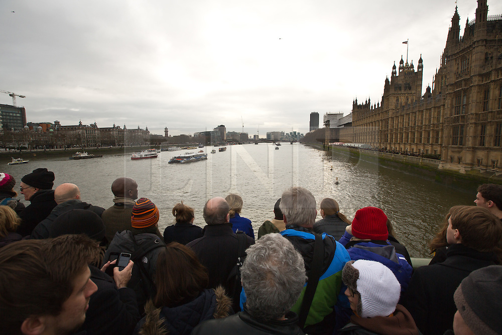 © Licensed to London News Pictures. 30/01/2015. The boat that carried Churchill's body on the day of his funeral fifty years ago has today retraced its movements on the Thames. In a poignant service with Churchill family members on board, the Havengore left HMS President at Wapping with a flotilla of vessels behind, passing under a raised Tower Bridge, passed HMS Belfast and proceeded to the Houses of Parliament where a wreath was cast in to the river in remembrance of Sr Winston. The cranes that so memorably dipped fifty years ago are no longer present along the river but HMS Belfast fired a 4 gun salute as the former PLA hydrographic survey vessel made its way up river. Credit : Rob Powell/LNP