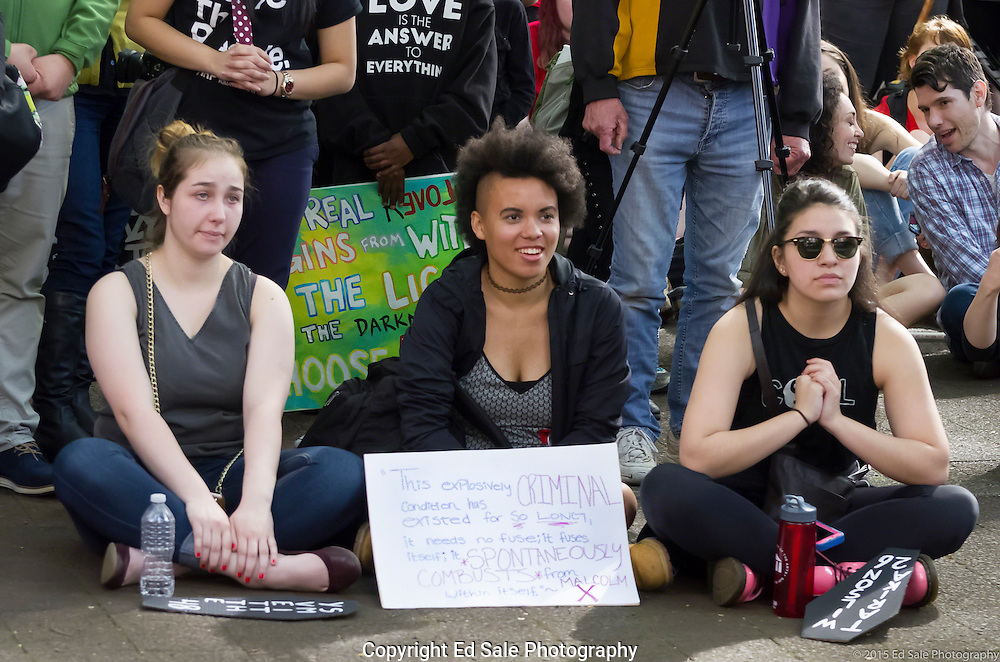 Three young students attend a 2015 May Day rally in Portland, Oregon appearing to be excited by the speaker.