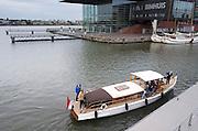 Een plezierboot legt voor het Bimhuis in Amsterdam aan bij een steiger.<br /> <br /> A boat is mooring at the quay near the Bimhuis in Amsterdam.
