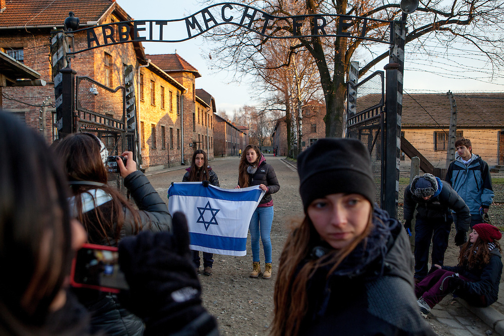 """A group of a students with a jewish flag are doing photographs under the sign """"Arbeit macht frei"""" at the entrance to the Auschwitz Nazi concentration camp. It is estimated that between 1.1 and 1.5 million Jews, Poles, Roma and others were killed in Auschwitz during the Holocaust in between 1940-1945."""