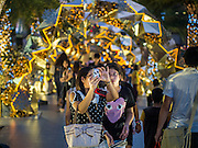 10 DECEMBER 2014 - BANGKOK, THAILAND: People photograph and walk among the Christmas lights at Paragon, a high end shopping mall in Bangkok. Thailand is overwhelmingly Buddhist. Christmas is not a legal holiday in Thailand, but Christmas has become an important commercial holiday in Thailand, especially in Bangkok and communities with a large expatriate population.         PHOTO BY JACK KURTZ