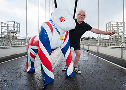 """© Licensed to London News Pictures; 06/08/2021; Bristol, UK. TONY MILES, aka SMILEY MILEY is photographed with a model gorilla called """"Jackorilla"""" wearing a replica Tokyo 2020 Olympic gold medal on the Clifton Suspension Bridge to say a great big thank you to Team GB for their excellent efforts in brining the medals back home from the Tokyo 2020 Olympic Games. The gorilla's union jack colours were designed and painted by Tony Miles, aka Smiley Miley from the Radio One Roadshow. Tony organised a fireworks display on the Clifton Suspension Bridge for the 2012 Olympic torch relay as it passed across the bridge. Photo credit: Simon Chapman/LNP."""