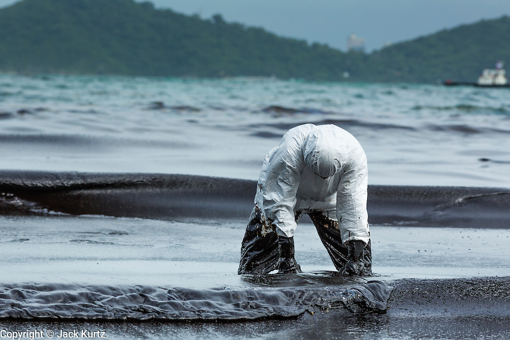 30 JULY 2013 - KOH SAMET, RAYONG, THAILAND:   A worker holds onto a vacuum device that sucks up oily water during oil spill cleanup on Ao Prao beach on Koh Samet island. About 50,000 liters of crude oil poured out of a pipeline in the Gulf of Thailand over the weekend authorities said. The oil made landfall on the white sand beaches of Ao Prao, on Koh Samet, a popular tourists destination in Rayong province about 2.5 hours southeast of Bangkok. Workers from PTT Global, owner of the pipeline, and up to 500 Thai military personnel are cleaning up the beaches. Tourists staying near the spill, which fouled Ao Prao beach, were evacuated to hotels on the east side of the island, which was not impacted by the spill. PTT Global Chemical Pcl is part of state-controlled PTT Pcl, Thailand's biggest energy firm.    PHOTO BY JACK KURTZ