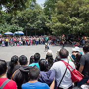 A street performer involves two small girls in his act and draws a large audience in Basque de Chapultepec, a large and popular public park in the center of Mexico City.
