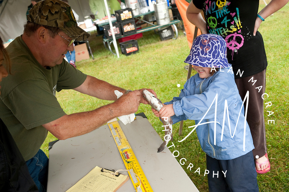 Five year old Chloe Sartory of Bartlett hands her catch over to Herb Ainsworth of the Belknap County Sportsman's Association for measuring during Sunday's Kids Fishing Derby at Gunstock Mountain Resort.  (Alan MacRae/for the Citizen)