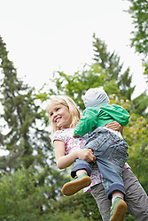 Young blonde girl carrying baby brother
