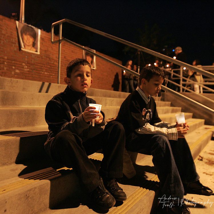 /Andrew Foulk/ For the North County Times/  .Cody Halbrook, 8, and his brother Derek, 10, hold candles as they sit below a photo of their family friend Amber Dubois during a Vigil to remember the fourteen year old at Escondido High School Monday night.