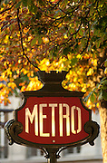 A classic Parisian metro sign underneath autumn leaves, Paris, France