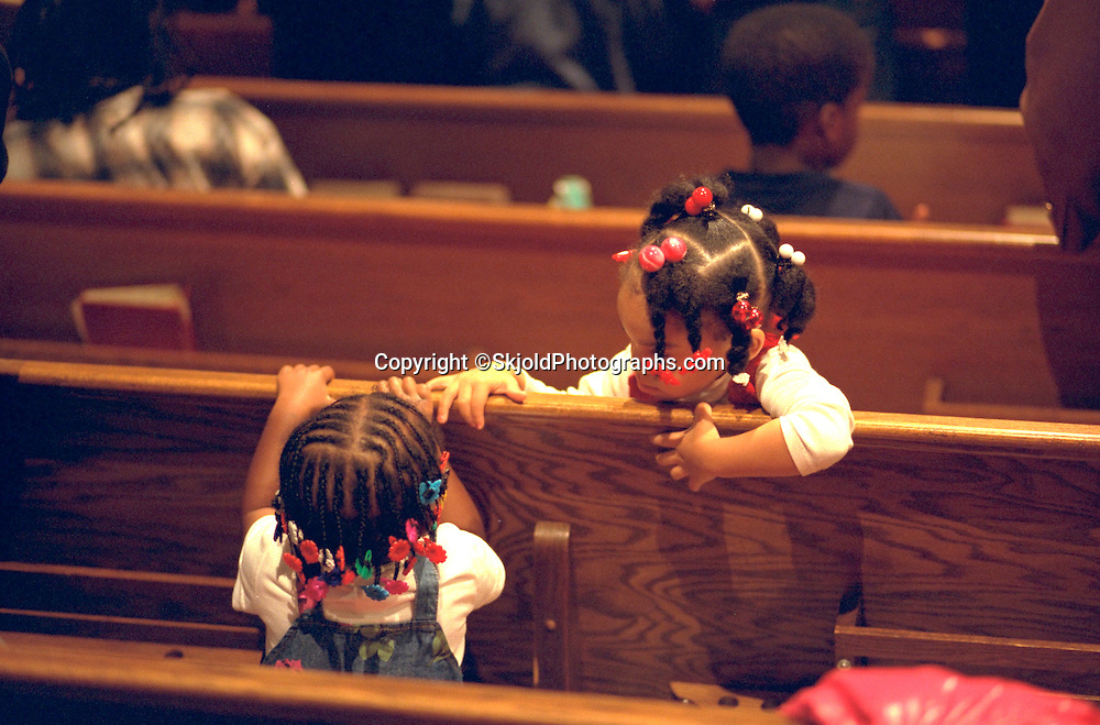 Friends age 3 talking during church service.  St Paul  Minnesota USA