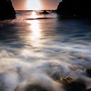 The sun sets over the Pacific Ocean near Carmel By The Sea, California.