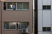 a Japanese salaryman smokes out of the window of an office inTokyo, Japan Friday, May 17th 2013