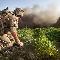 Corporal Price (Nicknamed SLICE for the machete he carries) runs towards a breach he has just blown in a compound wall using an explosive charge. An attachment of Royal Engineers( EOD specialists) and  B (Malta) Company 1st Battalion The Mercian Regiment undertake a 16 hour foot patrol to clear IED's (improvised explosive devices) around their base. The mission, which is one of the most dangerous tasks undertaken by the troops involved isolating suspected IED sites by blowing through compound walls and creating a cordon whilst the suspect site is examined and the any devices found are neutralized. The patrol left the base under the cover of darkness and worked throughout the day in searing temperatures reaching 55 C occasionally exchanging fire with the enemy. At nightfall the patrol retuned to base.  Nahr-e Saraj, Helmand Province, Afghanistan, 20th of August 2010.