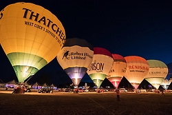 © Licensed to London News Pictures. 09/08/2018. Bristol, UK. The Balloon Nightglow with balloons firing their burners in time to music at the Bristol International Balloon Fiesta 2018 at Ashton Court estate which runs from Thursday 09 to Sunday 12 August. This year is the event's 40th anniversary and includes some special shape balloons that have not been seen for years, including Rupert the Bear (pictured) which has not been to the fiesta since the 1990s. A few balloons were inflated on Thursday evening but due to strong winds there was no mass ascent on Thursday evening. Photo credit: Simon Chapman/LNP