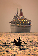 Fort Cochin, Kochi, Kerala, India, March 2008. Fishermen in a canoe make way for a cruiseship. Fort Cochin was colonialised by the Portugese, Dutch and British, It was an important port for the spice trade with the west. Photo by Frits Meyst/Adventure4ever.com