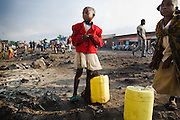 Children prepare to carry jericans of water back home in Goma, Eastern Democratic Republic of Congo on Monday December 15, 2008. Goma's Majengo neighborhood is almost entirely built on lava, after the nearby volcano erupted in 2002. As a result, there is no working water supply network, and residents, often children, must sometimes walk several kilometers to go buy water from tanks spread around the area.
