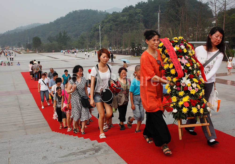 Visitors offer a flower reef to a statue of Mao Zedong at the Statue Square near Mao's birthplace in Shaoshan, Hunan Province, China on 12 August 2009.  The village of Shaoshan, in rural Hunan Province, is tiny in size but big in name. It was the childhood home for Mao Zedong, the controversial revolutionary who came from obscurity but eventually defied all odds conquered China in the name of communism. Now his home, a sacred place among China's official propaganda, is in reality a microcosm of the country itself: part commercialism, part superstition, with a dash of communist ideological flavor.