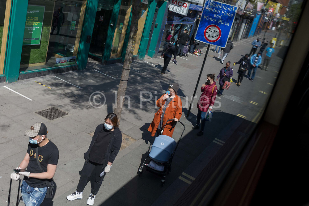 As the UKs Coronavirus death toll during the governments social distancing lockdown, rose by 384 to 33,998, and the R rate of infection is reported to be between 0.7 and 1.0, south Londoners queue for the Post Office on the Walworth Road in Southwark, on 15th May 2020, in London, England.