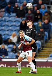 Burnley's Sam Vokes (left) and Barnsley's Liam Lindsay (right) battle for the ball during the Emirates FA Cup, third round match at Turf Moor, Burnley.