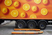 A long-distance lorry is parked at the Sainsbury's 700,000 sq ft (57,500sq m) supermarket warehouse and distribution depot at Waltham Point London England. With round wheels echoing the circles of oranges, long-distance vehicles depart every two minutes, 24 hours a day, 364 days a year to 80 UK stores and handling 2.5m supermarket cases a week. Transporting refrigerated perishable foodstuffs, these lorries are ever-present on the nation's motorways and A-roads, plying back and forth to re-supply the supermarkets. Food orders are conveyed with sorter systems that group products together, ordering them to favour the layout of specific stores, optimising how the shelves are stacked.