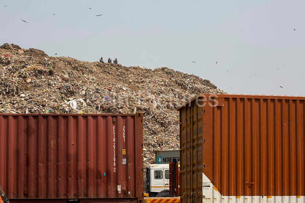 Three men sit at the top of Okhla landfill while birds fly around the dumping ground on 18th September 2018 in Okhla, Delhi, India, Asia. The site was decommissioned in 2018 after reaching three times the permissible limit.