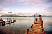 Early morning view of jetties with Volcanoes Toliman and Atitlan small canoe in distance from North shore line of Panajachel.