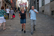 1 of 2 in a sequence showing a husband and wife messing around on a street where they attempt to race backwards on cobbles, on 20th July, in Porto, Portugal. In the first picture we see the man upright and confidently winning the race with the lady - while in the second, he has has fallen over completely, with legs in the air.